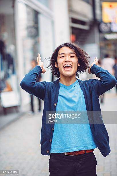Portrait of happy young japanese man outdoors