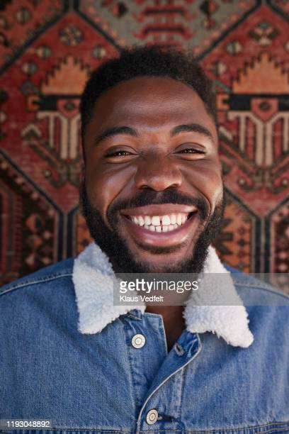 portrait of happy young man against patterned wall - black jacket stock pictures, royalty-free photos & images