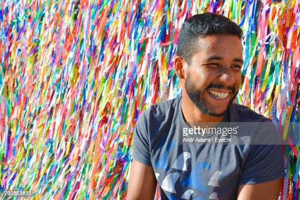 portrait of happy young man against streamers - streamer stock pictures, royalty-free photos & images