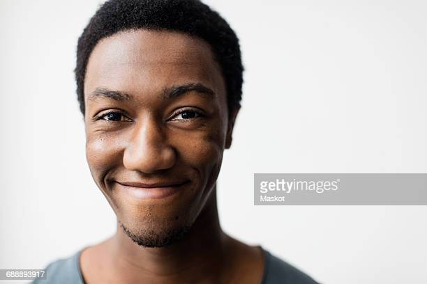 portrait of happy young man against white background - 18 19 anos - fotografias e filmes do acervo