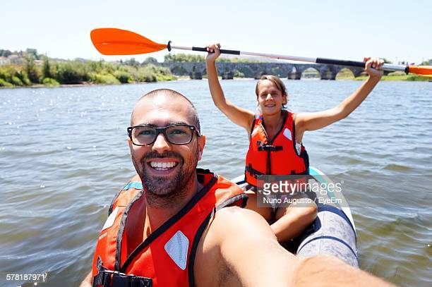Portrait Of Happy Young Man And Woman Kayaking On River