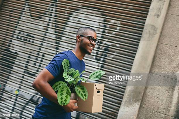 Portrait of happy young man carrying cardboard box and foliage plant