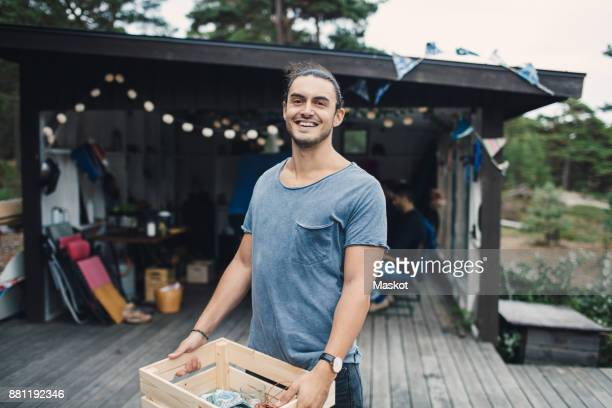 Portrait of happy young man carrying wooden crate on porch in back yard
