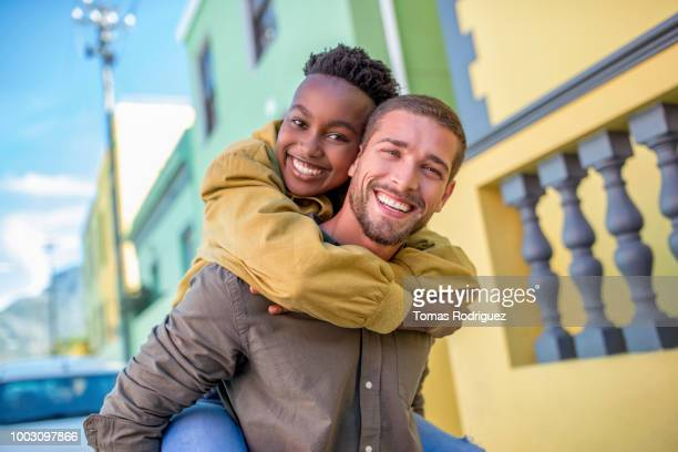 Portrait of happy young man giving girlfriend a piggyback ride