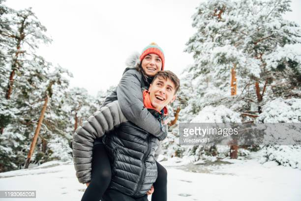 portrait of happy young man giving his girlfriend a piggyback ride in winter forest - padded jacket stock pictures, royalty-free photos & images
