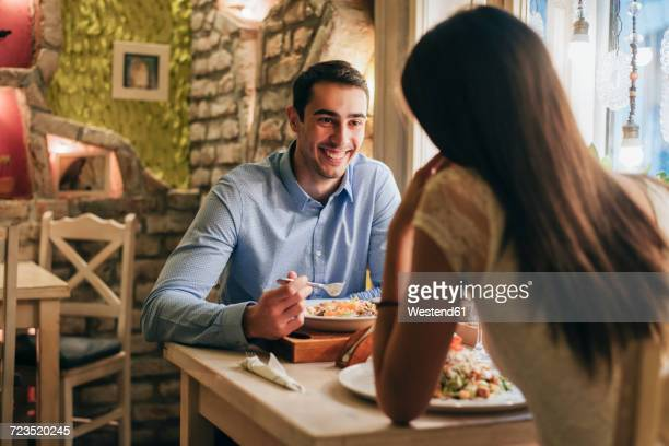 Portrait of happy young man having dinner with his girlfriend in a restaurant