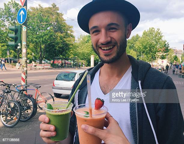 Portrait Of Happy Young Man Holding Smoothie At Street