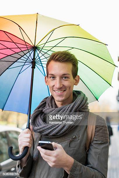 Portrait of happy young man holding umbrella and cell phone outdoors