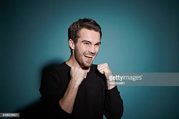portrait of happy young man in front of blue background - luck stock pictures, royalty-free photos & images