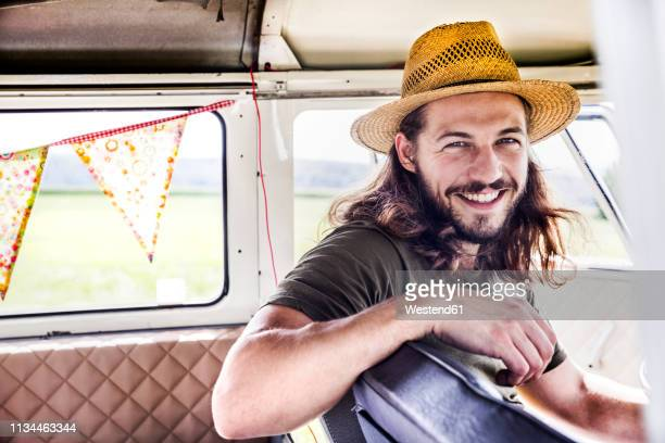 portrait of happy young man inside a van - langes haar stock-fotos und bilder