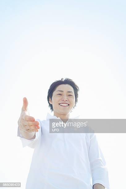 portrait of happy young man - 手を伸ばす 男性 ストックフォトと画像