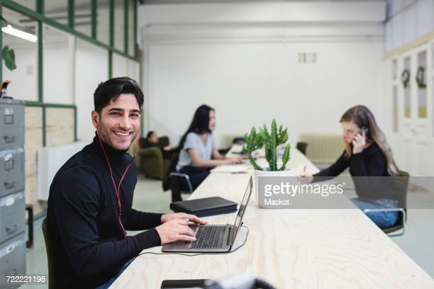 Portrait of happy young man sitting at desk with colleagues working in background