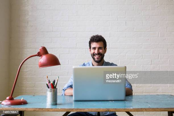 portrait of happy young man sitting at desk working with laptop - visão frontal imagens e fotografias de stock