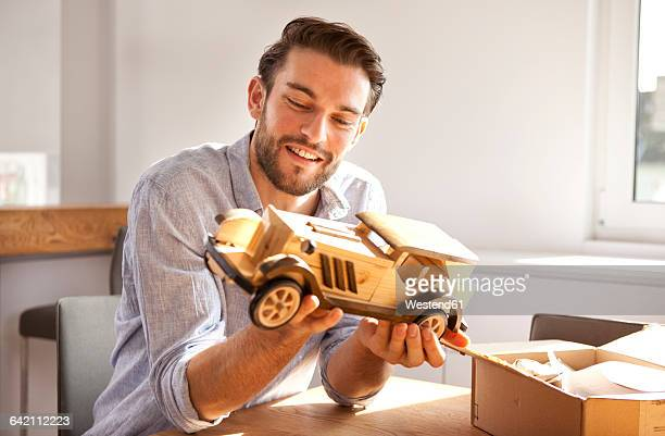 portrait of happy young man sitting at table looking at wooden toy car - toy box stock pictures, royalty-free photos & images