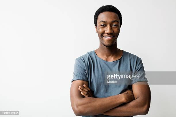 Portrait of happy young man standing arms crossed against white background