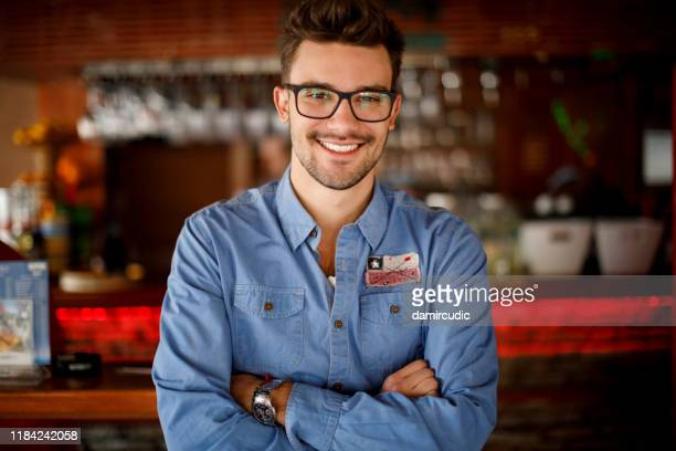 portrait of happy young man standing with his arms crossed in a coffee shop - franchising stock pictures, royalty-free photos & images