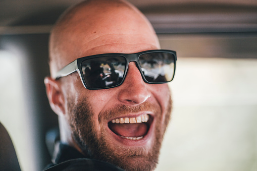 Portrait of happy young man with sunglasses and beard on a road trip - gettyimageskorea