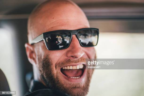 portrait of happy young man with sunglasses and beard on a road trip - サングラス 男性 ストックフォトと画像