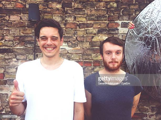 Portrait of happy young men standing against brick wall