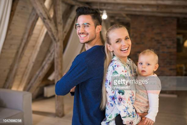 portrait of happy young parents with their baby girl at home - junge familie stock-fotos und bilder
