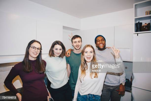 Portrait of happy young roommates standing in kitchen at college dorm