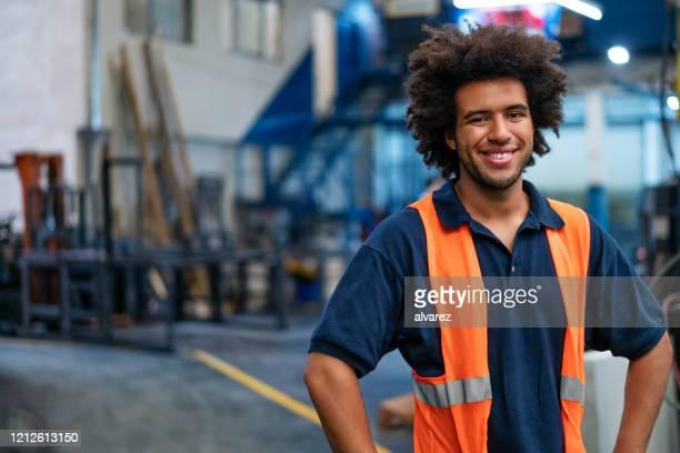 verticale du jeune ouvrier heureux d'entrepôt - origine ethnique photos et images de collection