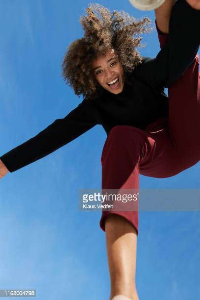 portrait of happy young woman against blue sky - low angle view stock pictures, royalty-free photos & images