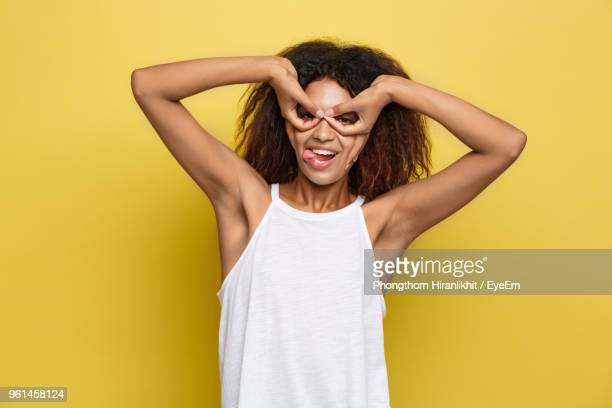 Portrait Of Happy Young Woman Against Yellow Background