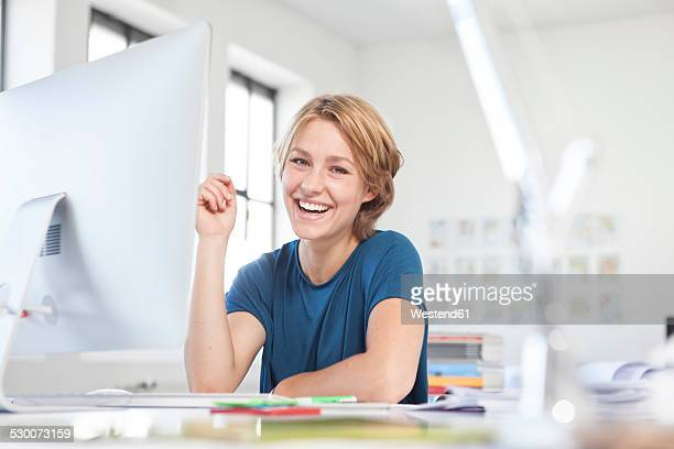 Portrait of happy young woman at her desk in a creative office