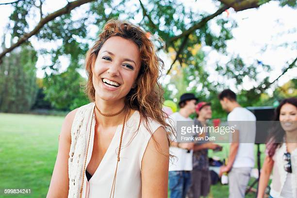 Portrait of happy young woman at sunset party in park