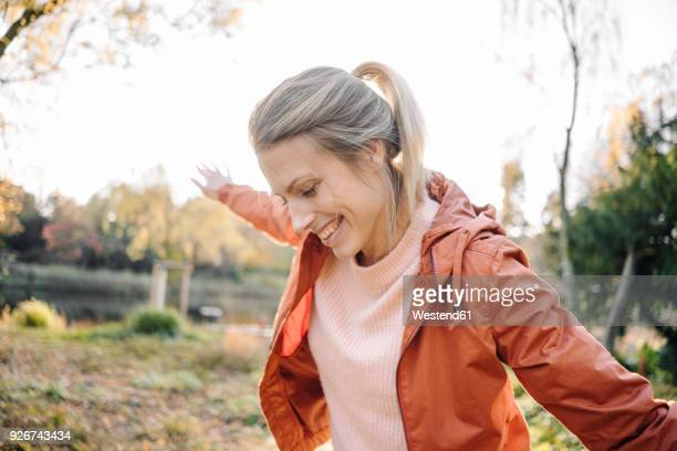 portrait of happy young woman balancing in autumnal park - beleza natural imagens e fotografias de stock