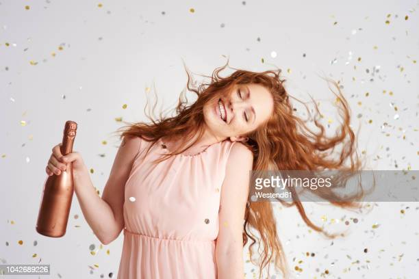 portrait of happy young woman dancing with bottle of champagne - festa donna foto e immagini stock