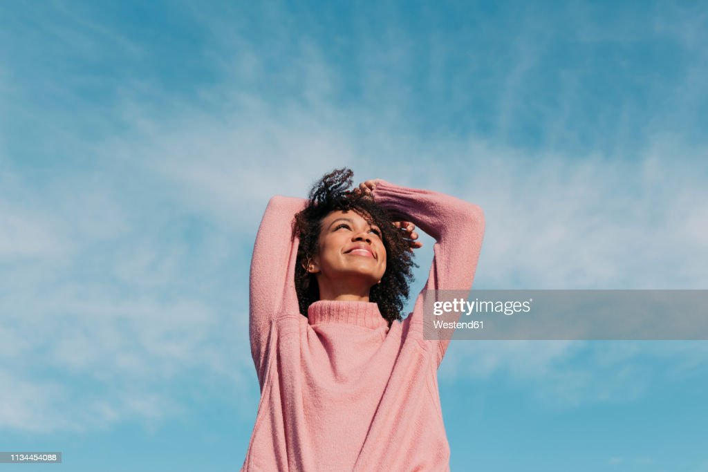 Portrait of happy young woman enjoying sunlight : Stock Photo