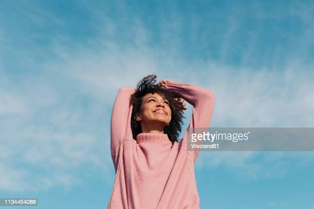 portrait of happy young woman enjoying sunlight - jumper stock pictures, royalty-free photos & images