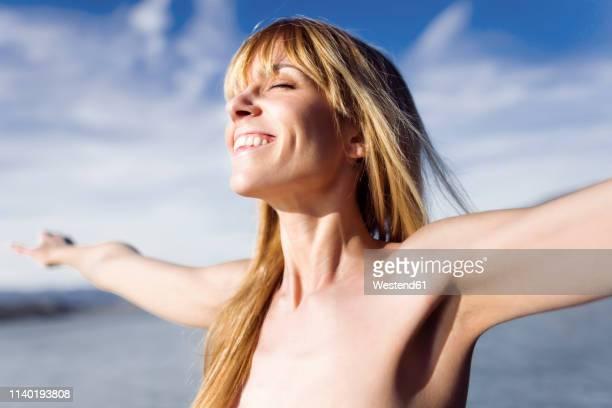 portrait of happy young woman enjoying sunlight - mujer desnuda naturaleza fotografías e imágenes de stock