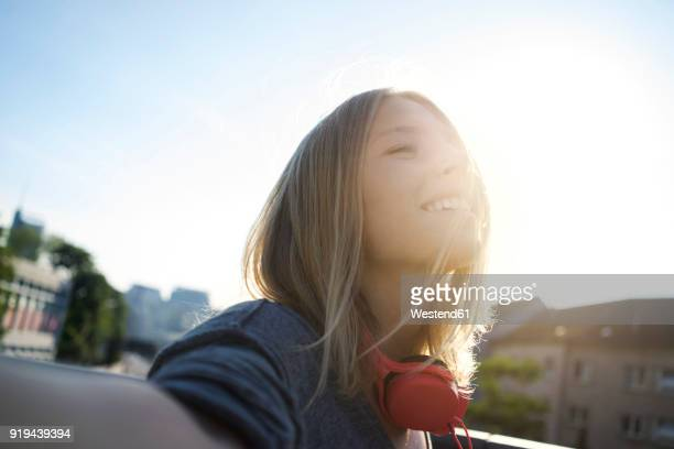 portrait of happy young woman enjoying sunlight - gegenlicht stock-fotos und bilder