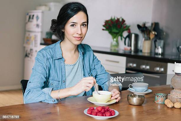 Portrait of happy young woman having coffee at table in kitchen