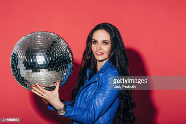 Portrait of happy young woman holding disco ball against coral background