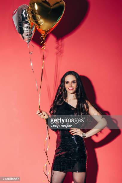 Portrait of happy young woman holding helium balloons against coral background