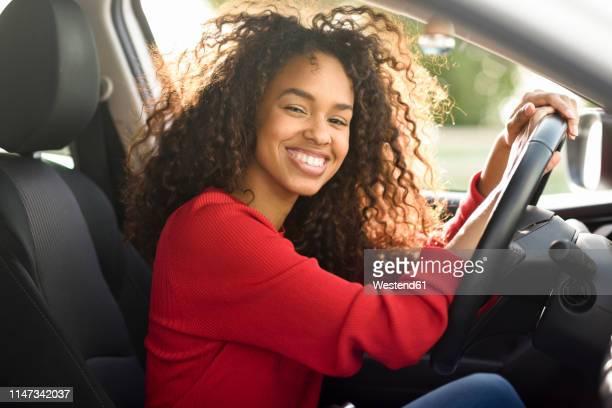 portrait of happy young woman in a car - conducteur métier photos et images de collection