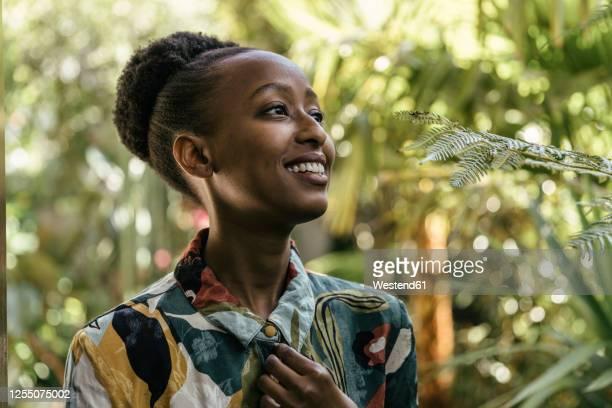 portrait of happy young woman in a garden - natürliches haar stock-fotos und bilder