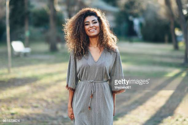 portrait of happy young woman in a park - dress stock pictures, royalty-free photos & images