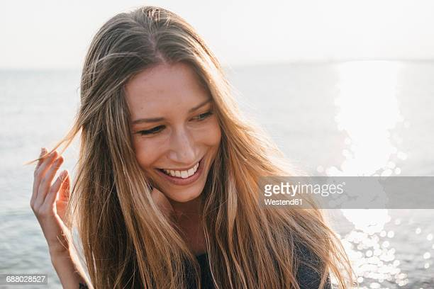 Portrait of happy young woman in front of the sea