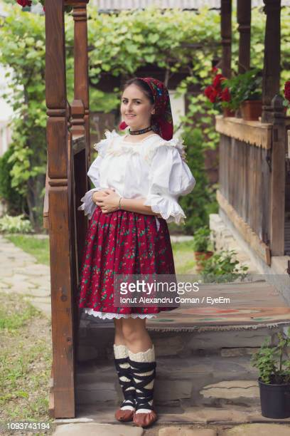 portrait of happy young woman in romanian clothing standing on porch - traditionelle kleidung stock-fotos und bilder