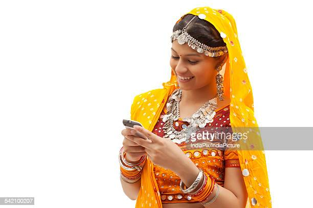 Portrait of happy young woman in traditional wear messaging on cell phone against white background