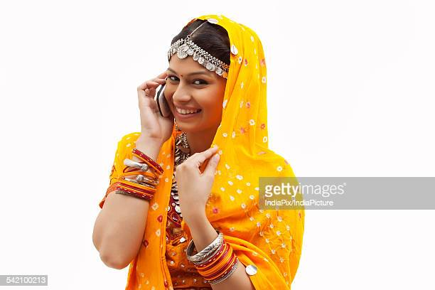Portrait of happy young woman in traditional wear using cell phone over white background