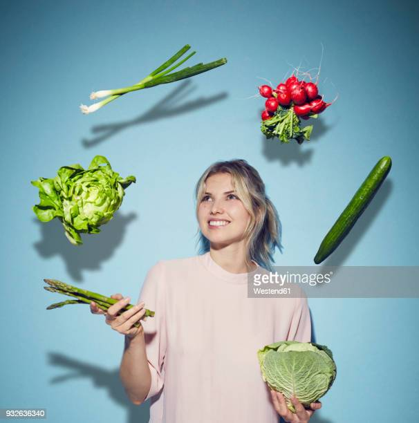 portrait of happy young woman juggling with vegetables - hovering stock pictures, royalty-free photos & images