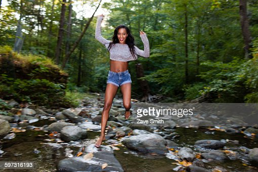 Portrait Of Happy Young Woman Jumping Over Forest River