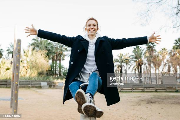 portrait of happy young woman on a seesaw on playground - arms outstretched stock pictures, royalty-free photos & images