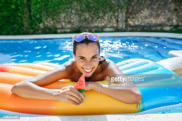 Portrait of happy young woman on airbed in swimming pool